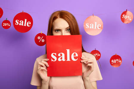 funny woman with raised eyebrow hiding behind the sale sign, isolated over blue background, studio shot.