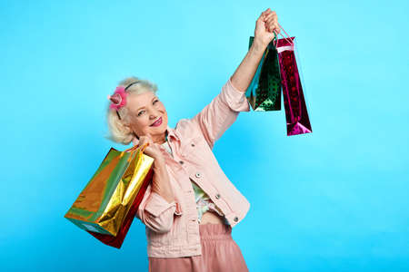 pretty granny has bought presents, clothes for her granddaughters and grandsons. close up portrait. isolated blue background. old shopaholic female