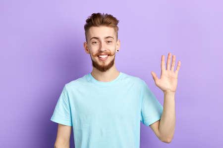Positiver fröhlicher Mann, der seine offenen Handflächen zeigt, menschliche Emotionen, Gesichtsausdrücke, gutaussehender Mann, der mit der Hand winkt, hallo, hallo, guten Abend, bis später. isolierter blauer Hintergrund, Studioaufnahme