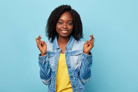 joyeuse fille américaine souriante a des expressions joyeuses, croise les doigts et sourit avec joie, porte des vêtements décontractés à la mode, isolée sur un mur bleu.geste, concept de langage corporel