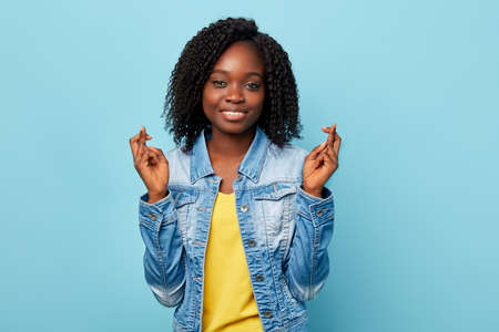 cheerful smiling American girl has joyful expressions, cross fingers and smile gladfully, wear casual trendy clothes, isolated over blue wall.gesture, body language concept