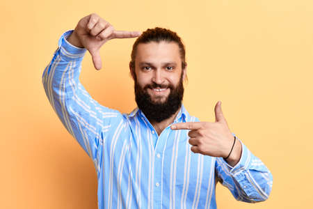 happy positive handsome young man making frame with fingers isolated on a yellow background. camera. man is pretending that he is taking a photo