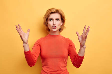 angry irritated frustrated woman with hands raised shouting at camera isolated on the yellow background. close up portrait, studio shot. feeling , emotion, facial expression