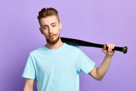 handsome serious hooligan with baseball bat isolated on blue background. close up portrait. lifestytle, free time, spare time. Banco de Imagens