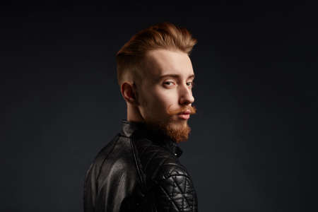 ginger young man with unusual appearance wearing trendy leather jacket. isolated black background. studio shot.copy space. close up side view photo