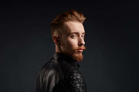 jengibre joven con apariencia inusual vistiendo chaqueta de cuero de moda. fondo negro aislado. Foto de estudio Espacio de copia. cerrar foto de vista lateral