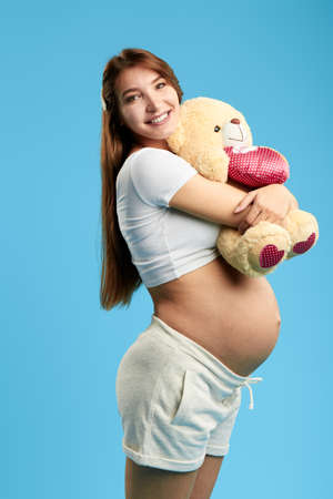 cheerful positive pregnant woman with her teddy bare posing to the camera. strong hug. isolated blue background. healthy pregnancy,
