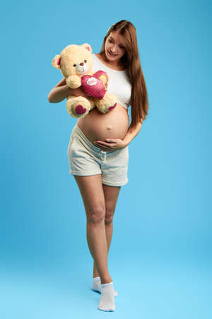 happy woman touching her belly while carring the bear. full length photo. fist present for baby. isolated blue background. studio shot