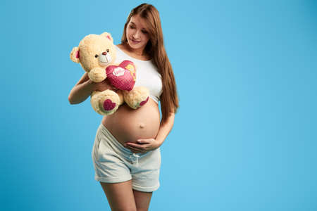 pregnant childish girl having fun with tedduy bear in the studio with blue wall, copy space , close up photo. childhood.