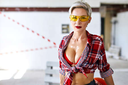 sexual builders will help you with building, design of room. close up photo. sexy blonde girl in yellow sunglasses, stylish checked shirt looking at the camera. copy space