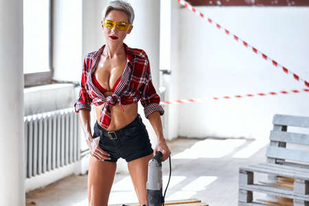 glamour carpenter with a hand in her pocket with hammer drill looking at the camera. laziness, rest copy space Stockfoto