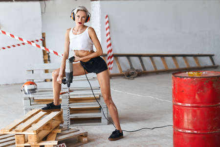 sexy serious slim girl in headphone working with perforator in the construction site, full length photo. copy space. job, occupation
