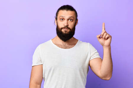 Attractive unshaven young man in white t-shirt pointing up with his finger isolated on blue background. close up portrait. isolated blue background.gesture, body language