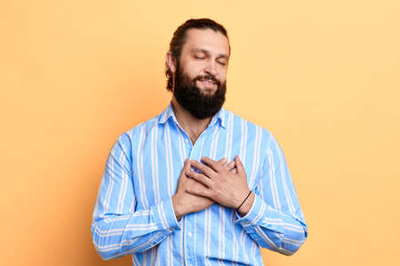 emotional romantic loving man with closed eyes in stylish striped shirt touching his heart , fell in love, strong feeling.