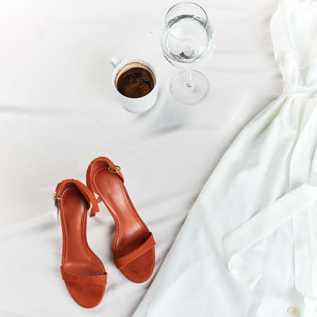 comfortable orange sandals, cup and glass, white linen dress. top view cropped photo.trendy footwear