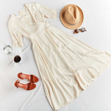 white long dress and brown leather shoes on white background. Fashionable summer outfit concept. top view Stockfoto