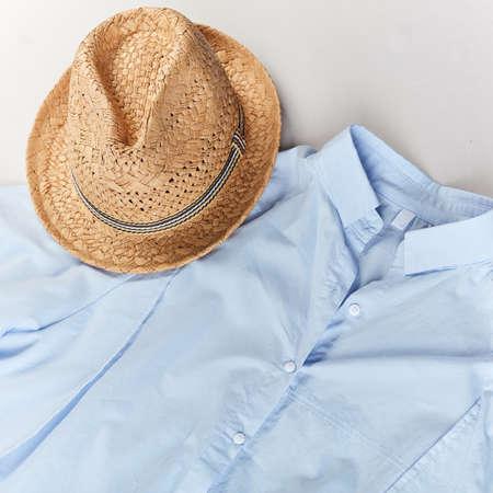advertisement of stylish straw hat. hat and light blue shirt on white background.shopaholics bargain concept
