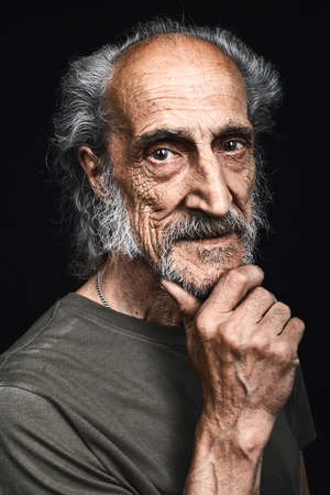 old homeless person with a hand on chin thinking about problem, pensive expression.Doubt concept. man has a lot of difficulties in life. studio shot. isolated black background Zdjęcie Seryjne - 131714802