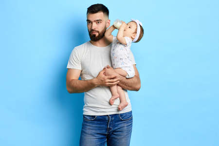 pensive thoughtful guy holding a girl in hands, while she is drinking milk, close up photo, dinner time, healthy food for baby,