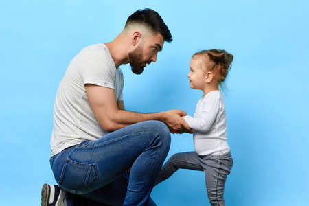 caring father and little obedient daughter who listens to the instruction of parent on blue isolated background. daddy making an observation to kid. dad asking daughter to behave well Stock Photo