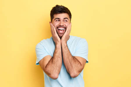 amazed positive cheerful man in casual clothing screaming in surprise or delight and touching cheeks, looking aside isolated over yellow background, success, happiness, positive feeling ad emotion