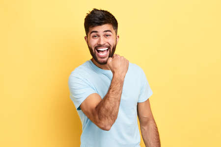 overjoyed man has achieved his goal, happiness, close up portrait, isolated yellow background, studio shot.
