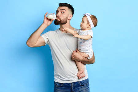 Young crazy father checking milk before giving it to kid. close up photo. isolated blue background. studio shot.funny greedy daddy drinking from the babys bottle.