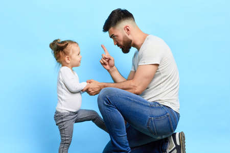 daddy scolding his little stubbon naughty daughter for her bad behaviour. family generations problems, misunderstanding concept. isolated blue background. studio shot.generation gap. punishment