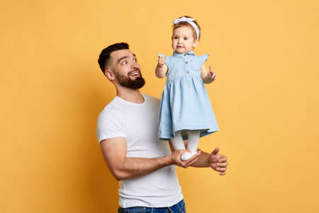 Happy unforgettable moments, excited handsome man rejoicing at his daughters achievment. daddy teaches his daughter to stand, doing exercises. happy man looking at little girl who standing on palms