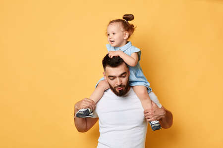 happy lovely girl in stylish dress riding a daddy like a horse. close up photo. happy moment. isolated yellow background. studio shot