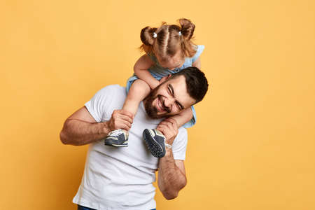 awesome positive man having fun with his little sister. isolated yellow background.entertainment.best time. unforgettable moments