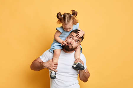 naughty girl throwing a tantrum, doing confusing things, kid pulling her dads face, skin, making fun of elder brother, mocking her dad. close up photo. isolated yellow background 写真素材