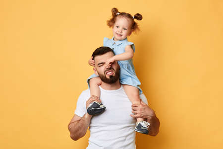 naughty girl holding her daddys nose, display negative, angry behaviour. close up photo. isolated yellow background.father cannot manage with naughty behaviour