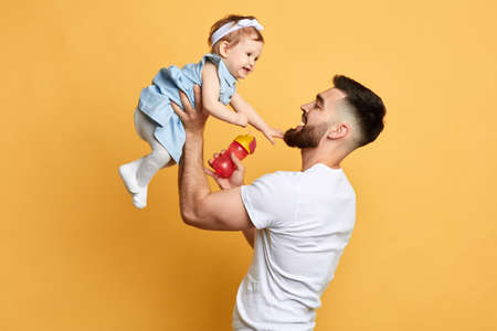 happy father holding his little kid in hands isolated over yellow background, family, love,warm relationship. close up side view photo.feeling and emotion