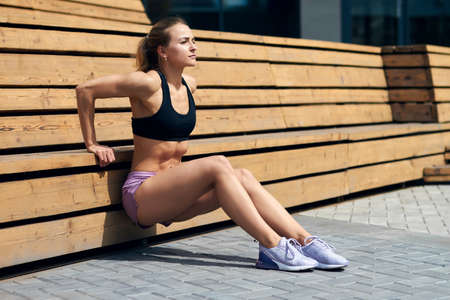 Young woman in stylish sportswear doing exercises in the street, free time, spare time, lifestyle , full length side view photo