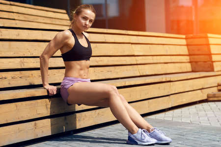 strrong muscular girl pumping the abdominals while sitting on the wooden bench. full length side view photo.copy space. Stock Photo