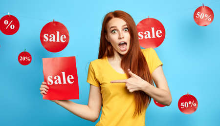 puzzled excited beautiful ginger girl pointing to the sheet of paper with the word sale. emotional saleswoman showing sales.close up photo. isolated blue background. studio shot Imagens