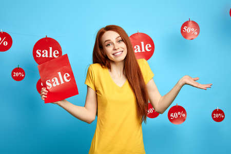 awesome lovely woman shrugging shoulders while having hesitations about sales, Uncertain female with a sheet of paper standing over blue background. girl doesnt know about sales and discounts