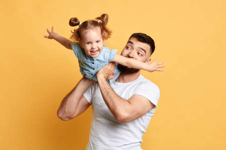Family holiday and togetherness. caring dad playing with a daughter. happiness, happy moment with parent. isolated yellow background. fun and joy