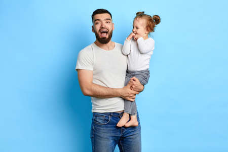 funny father singing songs to his kid. entertainmnet concept. isolated blue background.best father. happy parenthood