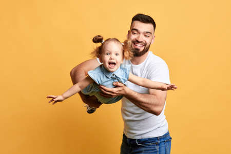 excited dad and his daughter looking at the camera while having fun. close up photo. isolatedyellow background. studio shot, happiness concept
