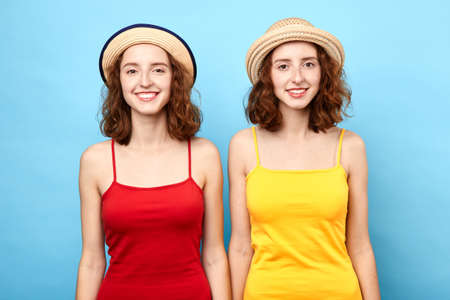 two beautiful women in straw hats posing to the camera. relationship, family concept. love, friendship