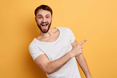 positive guy with wide open mouth indicates at copy space. hurry up, sale. close up portrait. isolated blue background. studio shot. emotion and feeling