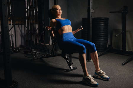 slim girl with perfect, ideal body is fond of sport. full length side view photo. weight training, equipment