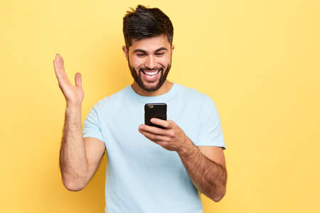 cheerful positive overjoyed man holds smart phone, reads something funny, raises palm,People and technology concept. close up portrait, isolated yellow background, studio shot