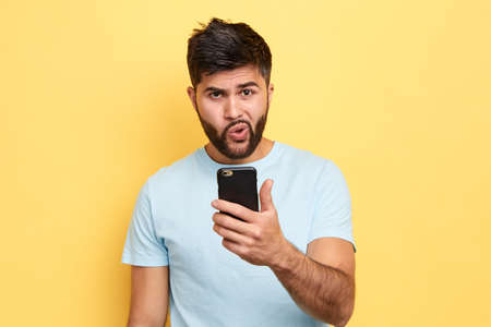 puzzled guy using his mobile phone. close up portrait. young bearded man has problems with gadget, trying to solve it. broken phone