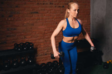 attractive fair-haired fit girl with slim weist, flat stomach doing exersises with weight. close up side view photo. sport, girl is fond of cross fit