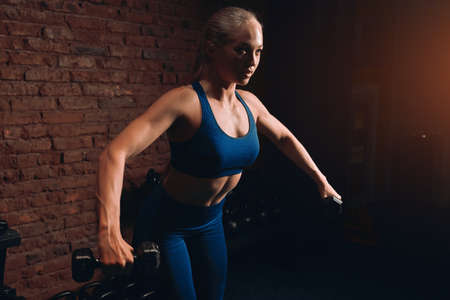 slim muscular blonde woman doing exercises for abdorminal muscles at gym with loft interior, close up side view photo.