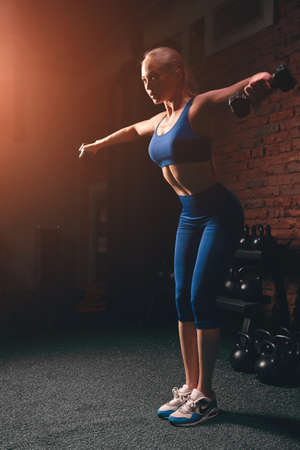 attractive awesome girl working out to have slim muscular body, doing exercises for arms. full length side view photo Stock Photo