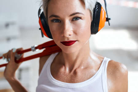 tired exhausted blonde girl in headphones with beautiful makeup in white top has drops on her shoulders and neck, she looking at the camera. close up photo.